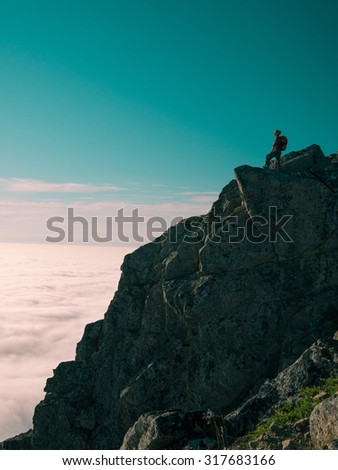 Toned image adult woman with a backpack stands on the edge of a cliff and looking at the sunrise against the blue sky and thick clouds floating down - stock photo