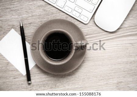 Toned image, cup of black coffee, pen, blank sheet of paper, mouse and  keyboard on wooden table