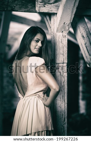 Toned image of a glamorous young woman in an old building - stock photo