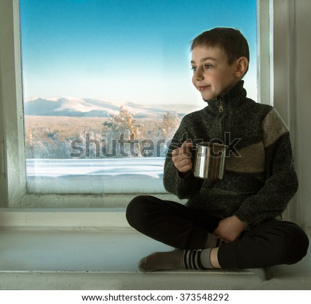 Toned image of a little boy sitting on an old window sill next to the window and holding in his hand a metal cup against the background of the winter mountains and blue sky - stock photo