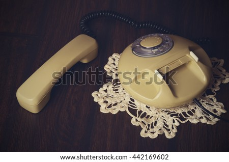 toned image of an old-fashioned phone and knitted napkin on a dark wooden table. top view, horizontal image - stock photo