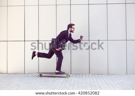 Toned image of businessman in black business suit on longboard walking with cup of coffee in his hand. Freelance man hurrying to his office. - stock photo