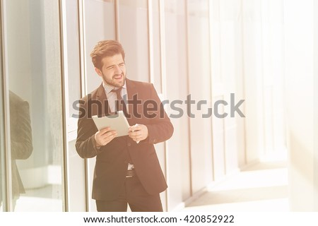 Toned image of businessman or freelancer walking along street with tablet PC in his hands. Happy man in business suit looking away in distance. - stock photo