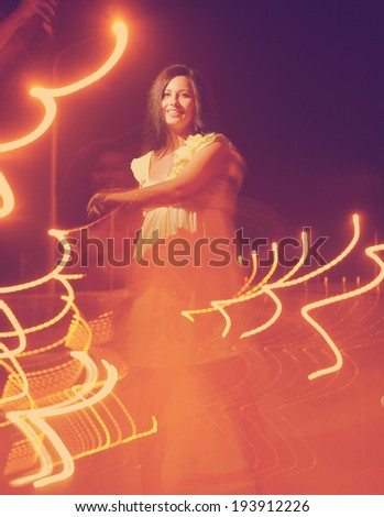 Toned image of dancing women  with lightpainting, long time exposure - stock photo