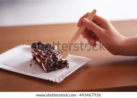 Toned image of delicious piece of chocolate cake represented on plate. Someone eating cake with fork.