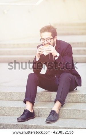 Toned image of handsome businessman in glasses eating junk food while sitting on stairs in city centre. Freelance man in black business suit. Side view. - stock photo