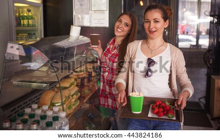 Toned image of happy ladies choosing dishes for eating. Cheerful women having break in cafe or restaurant. Sandwiches and snacks concepts.