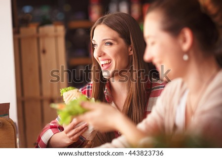 Toned image of happy smiling best friends spending free time in cafe or restaurant. Beautiful ladies eating vegetarian dishes and foods. - stock photo