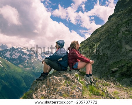 Toned image of offended men and women sitting on the rock back to back on a background of mountains and sky with clouds - stock photo