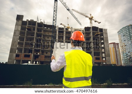 Toned image of young construction engineer reading blueprints at building site