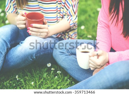 Toned image of Young women drinking coffee at park and enjoying summer day - stock photo