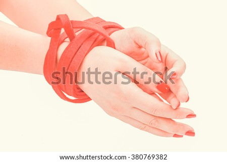 Toned photo. Color tone tuned. Bound woman hands red rope  - stock photo