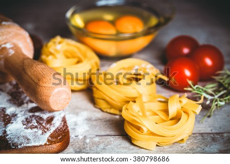 Toned photo. Color tone tuned. Homemade tagliatelle. Raw pasta on the wooden table. Selective focus. - stock photo