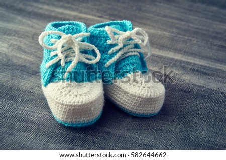 Toned photo of blue crocheted child bootees on wooden background.