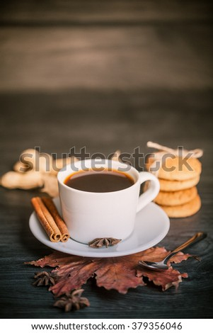 Toned photo of cup of hot tea on wood background with leaf. Autumn.