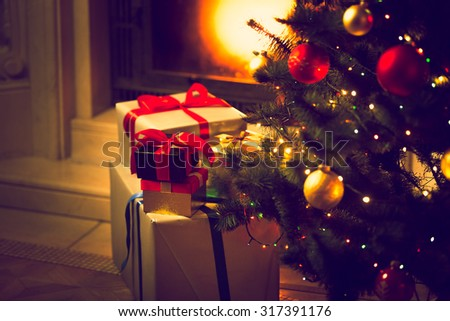 Toned photo of decorated Christmas tree and gift boxes against burning fireplace - stock photo