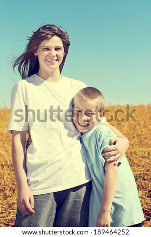 Toned photo of Happy Brother and Sister at the Wheat Field - stock photo