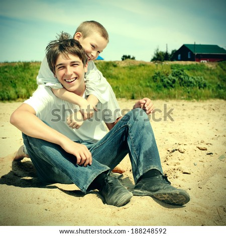 Toned photo of Happy Teenager and Kid on the Beach - stock photo