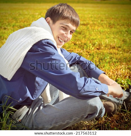 Toned photo of Happy Teenager sitting in the Autumn Field
