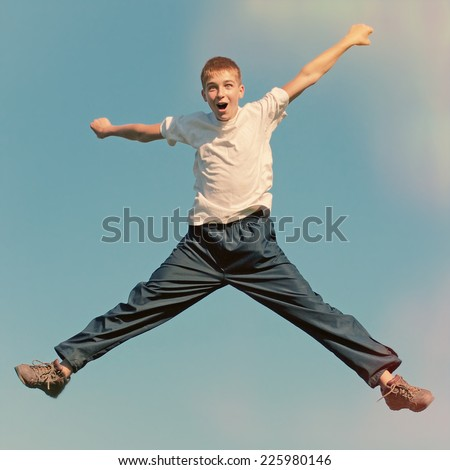 Toned photo of Happy Tennage Boy jumping on the Sky Background - stock photo