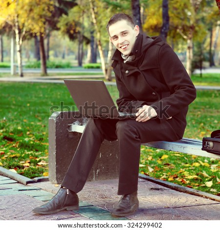 Toned Photo of Joyful Young Man with Laptop in the Autumn Park - stock photo