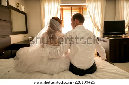 Toned photo of just married couple sitting on big bed at house - stock photo