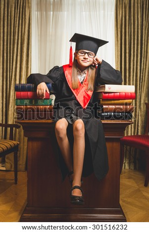 Toned photo of little girl in graduation cap posing on table at library - stock photo