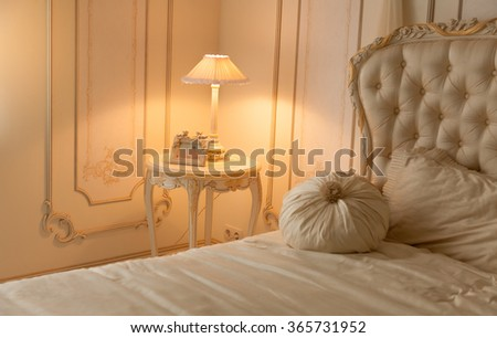 Toned photo of luxurious bedroom with lamp on bedside table - stock photo