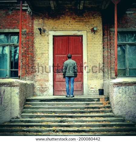 Toned photo of Man stand before Old House with closed Door - stock photo