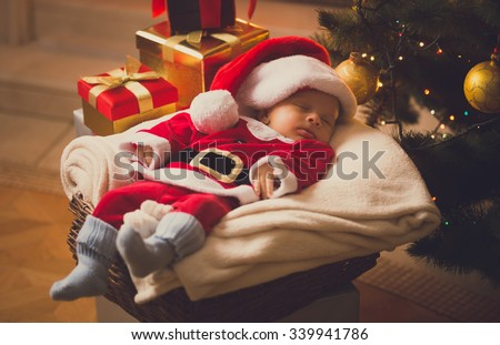 Toned photo of newborn baby boy dressed in Santa costume lying with Christmas gifts - stock photo