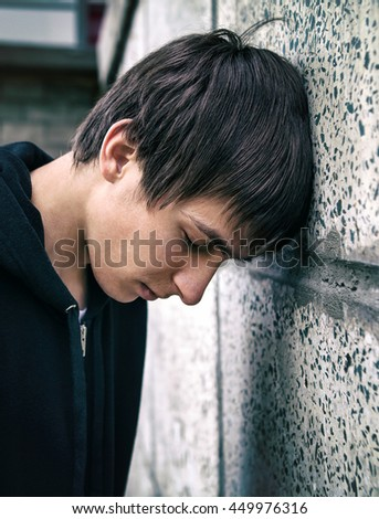 Toned Photo of Sad Teenager by the Wall outdoor - stock photo