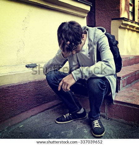 Toned Photo of Sad Young Man sit on the Porch of the House - stock photo