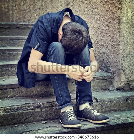 Toned Photo of Sad Young Man sit on the Street - stock photo