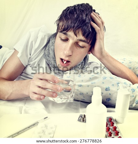 Toned Photo of Sick Young Man taking a Pill on the Bed - stock photo