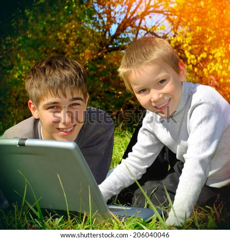 Toned photo of Teenager and Kid with Laptop outdoor - stock photo