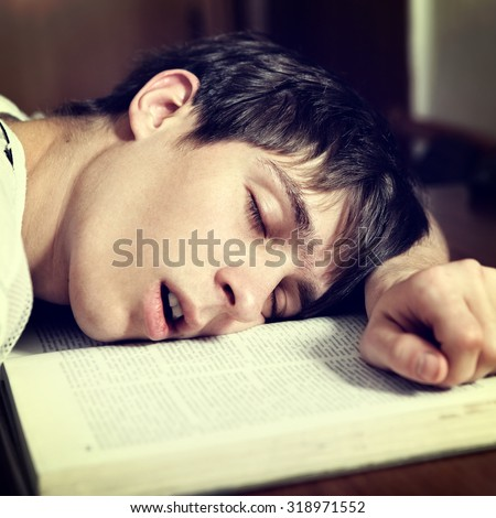 Toned Photo of Young Man sleep on the Book at the Home closeup