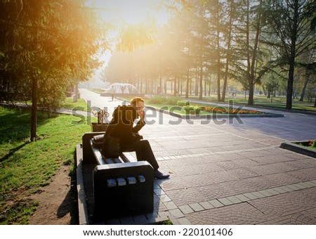 Toned photo of Young Man with Mobile Phone at the Autumn Park - stock photo
