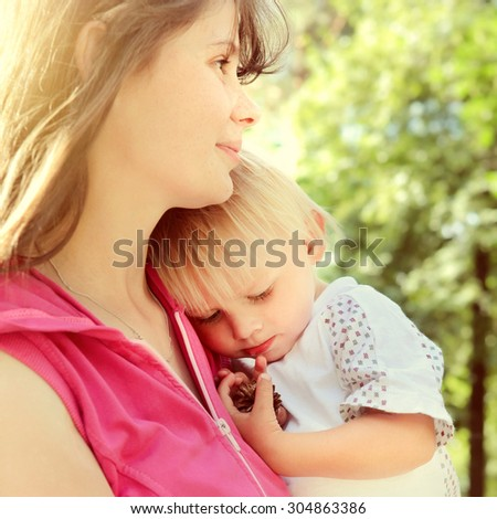 Toned Photo of Young Mother and Tired Child in the Summer Park - stock photo