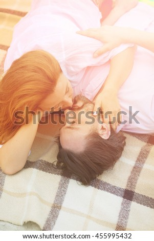 Toned picture of attractive mature couple relaxing on beach near by sea. Beautiful people kissing and enjoying their free on beach. - stock photo