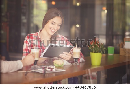 Toned picture of beautiful lady using tablet PC while sitting in cafe or restaurant and smiling. Woman drinking coffee and eating sandwich.