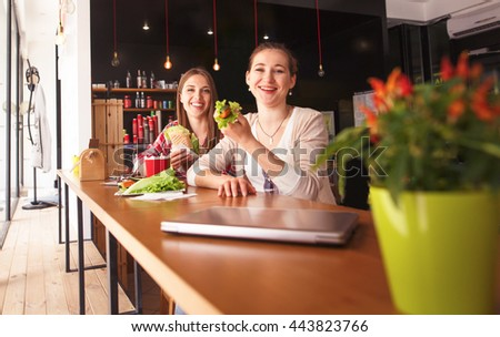 Toned picture of best friends eating vegetarian sandwiches in cafe or restaurant while looking at camera. Freelance concept. - stock photo