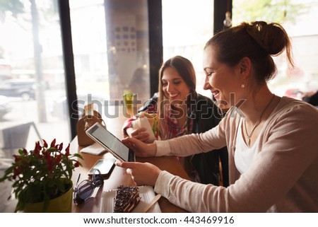 Toned picture of best friends ladies smiling while spending their free time in cafe. Beautiful women using tablet PC and mobile or smart phone. - stock photo