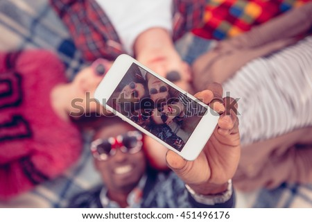 Toned. Picture of best friends making selfie on mobile or smart phone while spending free time on picnic in parkland. - stock photo