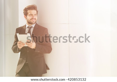 Toned picture of businessman or freelancer walking along street. Handsome man standing with tablet PC in his hands near office building. - stock photo