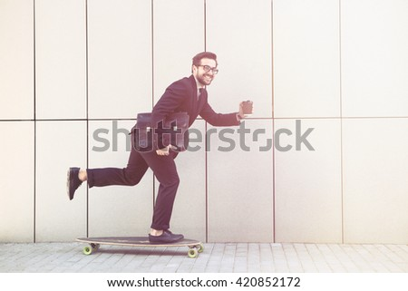 Toned picture of confident businessman smiling for camera and going to his office on longboard. Freelance man holding cup of coffee. - stock photo