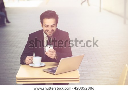 Toned picture of happy businessman using mobile phone and drinking coffee or tea in restaurant or cafe. Freelance man working on his laptop computer. - stock photo
