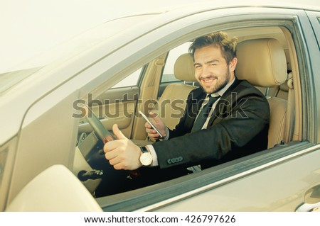 Toned picture of happy smiling businessman driving car and holding mobile or smart phone in front of him. Handsome freelance man working on to go. - stock photo