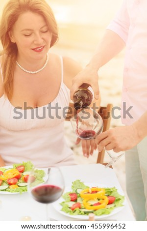 Toned picture of professional sommelier demonstrating red wine to beautiful woman. Red-haired woman looking at sommelier pouring red wine in her glass. - stock photo