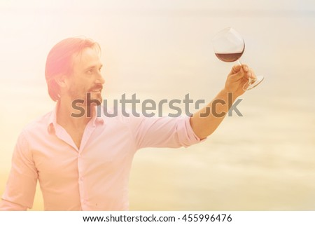 Toned picture of satisfied mature professional sommelier looking at glass with red wine. Handsome man in pink shirt drawing aside glass. - stock photo