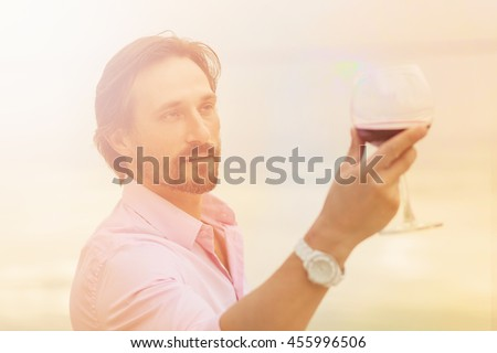 Toned picture of sommelier analyzing a glass of red wine isolated on blue sky background. Black-haired mature man happy looking at glass. - stock photo